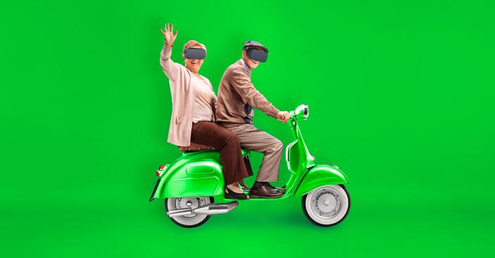 couple de seniors assis sur un scooter et portant un casque de réalité virtuelle